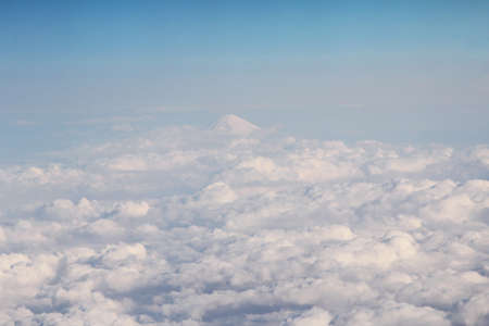 Clouds on sky and the Fuji peak above the airspace of Japan photo from airplane window
