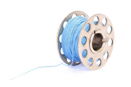 Closeup image of blue sewing thread on a white background