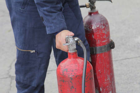 Firefighter  training to use a fire safety tank in a fire drill. Stock Photo