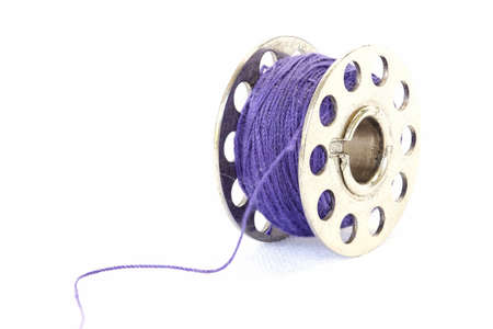 Closeup image of purple sewing thread on a white background Stock Photo