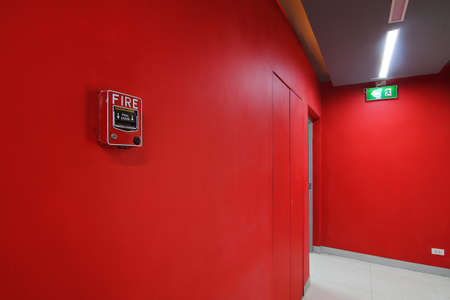 Emergency exit of the building with fire exit sign and fire alarm