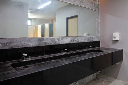 Sinks inside the public toilet, public bathroom. They are not clean and dusty Stock Photo