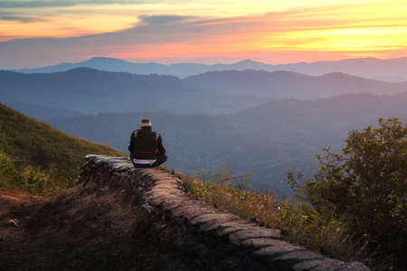 Traveler sightseeing the beautiful scenery of nature during sunset at Nern Chang Suek Mountain, Kanchanaburi province in Thailand. Travel and natural Concept Stock Photo
