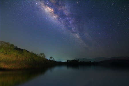 Milky way and many stars on night sky at at lake and mountain in Thailand.