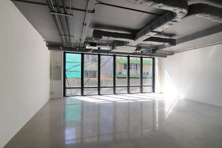 Empty office room on modern building with sunlight and indoor ventilation system on hight ceiling of large building