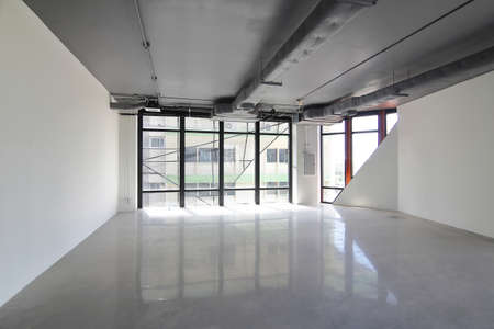 Empty office room on modern building with sunlight and indoor ventilation system on hight ceiling of large building.