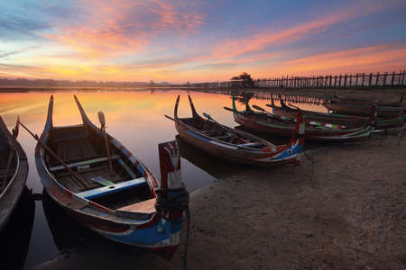 Beautiful scenery during sunset of marina at U-Bein bridge with colorful sky at Mandalay in Myanmar. This is a very popular for photographers and tourists. Attractions and transportation Concept.