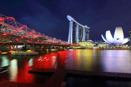 Singapore - July 31, 2017: Helix bridge and Marina Bay Sand during twilight time is famous landmark and very popular for photographers and tourists of Singapore city