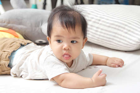 Bright eyes and innocent of asian little child on the bed in bedroom at home Stock Photo