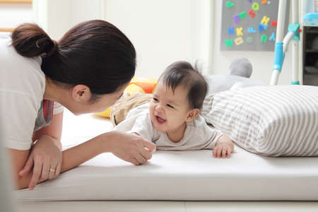 Little baby smiled and laughed happily with mother. Mom and baby boy teasing and relaxing at home.
