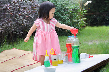 Little girl are enjoying with different water colors mixing for learning and strengthen Imagine. Stock Photo