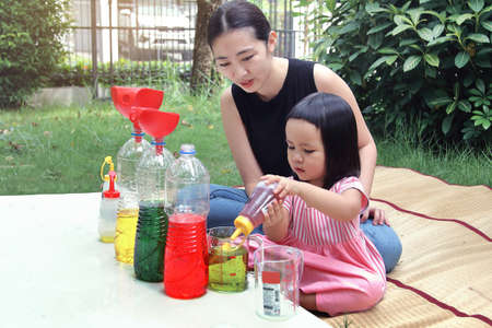 Asian mom and little daughter experiment with different water colors mixing for learning and strengthen Imagine. Stock Photo