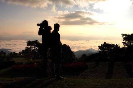 Silhouette of Asian couple tourist are take a photos beautiful scenery during sunrise at Huai Nam Dang National park,Chiang Mai in Thailand. Attractions and travel concept.