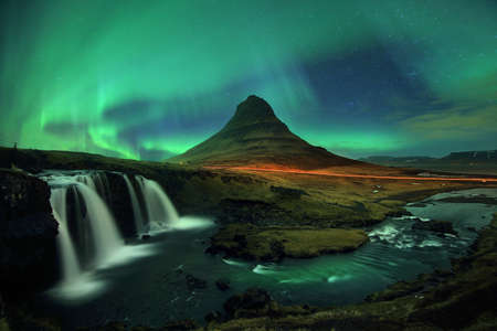 Beautiful scenery of Northern lights (Aurora Borealis) on night sky over Kirkjufell mountain and Kirkjufellfoss waterfall in Iceland. Long exposure shooting and high iso used make this photo have noise