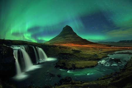 Piękna sceneria zorzy polarnej (Aurora Borealis) na nocnym niebie nad górą Kirkjufell i wodospadem Kirkjufellfoss w Islandii. Fotografowanie z długim czasem naświetlania i wysokie ISO sprawiają, że to zdjęcie ma szum