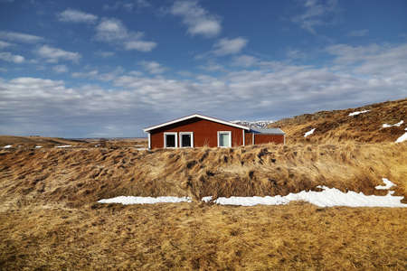 Residence among beautiful nature surrounded by meadow and blue sky in countryside at Iceland. Can be seen along the route on Ring road in Iceland.