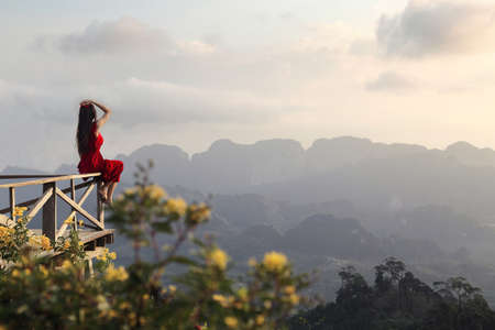 Rear view of a female tourist in a red dress sitting and watching the beautiful scenery during sunrise of Doi Tapang (Doi Ta Pang) Viewpoint at Chumphon province in Thailand. Stock Photo