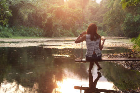 Female tourists sit and rest among beautiful nature park during sunset. Relaxation and travel concept
