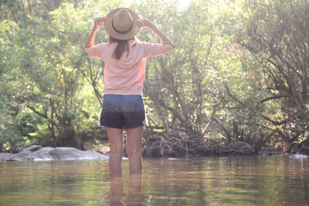 Female traveler relaxing among beautiful nature park. Relaxation and travel concept