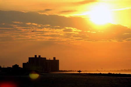 Sunrise and surfer in silhouette at Rockaway Beach photo