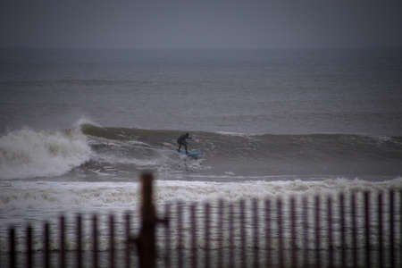 Surfer cruising on a wave. Photographed in Rockaway Beach, New York on December 29, 2015. Imagens