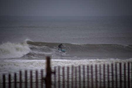 Surfer cruising on a wave. Photographed in Rockaway Beach, New York on December 29, 2015. Stok Fotoğraf