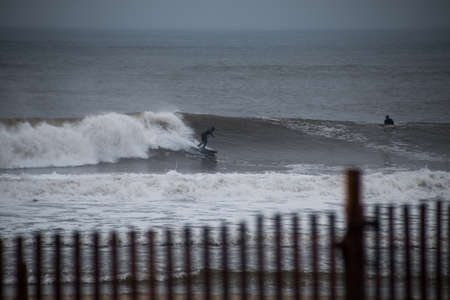 Surfer cruising on a wave. Photographed in Rockaway Beach, New York on December 29, 2015. Фото со стока