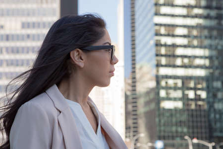 Young latin professional woman with glasses in the city. Photographed in NYC in November 2015