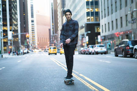Young skateboarder cruising donw the city street before sunset. Photographed in New York City in Feb 2016. Stok Fotoğraf