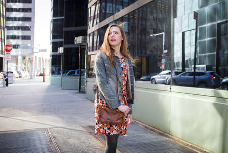 stride: Young professional Caucasian woman walking on city street on a bright sunny day