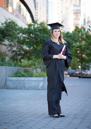 full figure: Portrait of female college student in graduation cap and gown holding diploma on campus Stock Photo