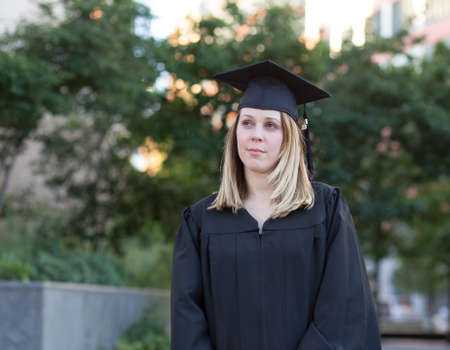 Portrait of female college student on campus in graduation day, looking worried and confused