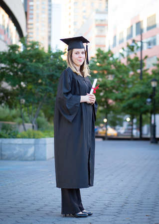 Portrait of female college student in graduation cap and gown holding diploma on campus Stock Photo