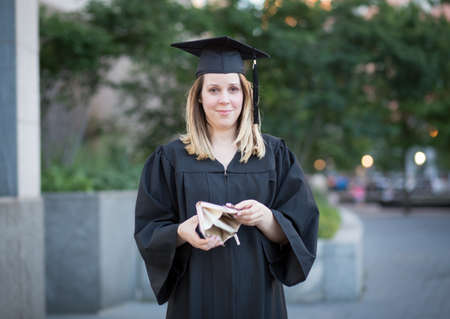 Portrait of female college student in graduation day, broke and in debt Stock Photo