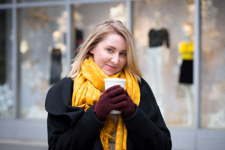 christmas lights display: Winter portrait of young Caucasian woman drinking hot chocolate, photographed in NYC in December