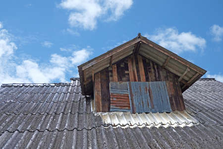 Tiled roof with attic windows against the blue sky