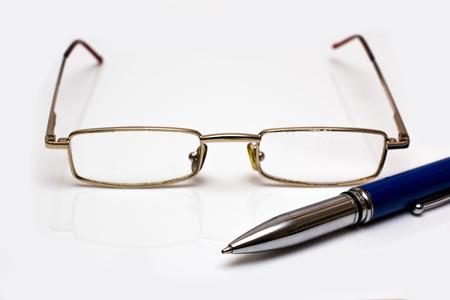 Glasses and pen on white Zdjęcie Seryjne
