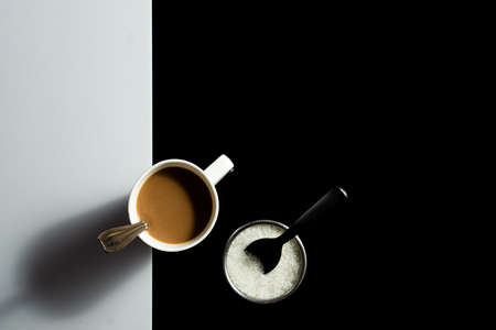 A cup of tea and and sugar with work space around on a black and white background