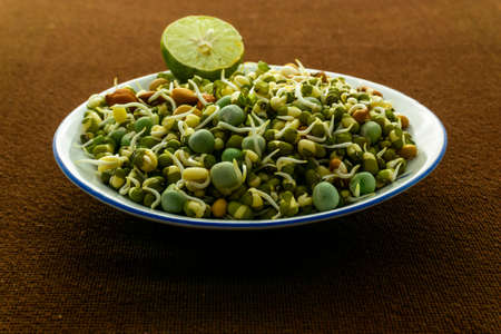 Healthy Sprouts in a white plate placed on a brown background