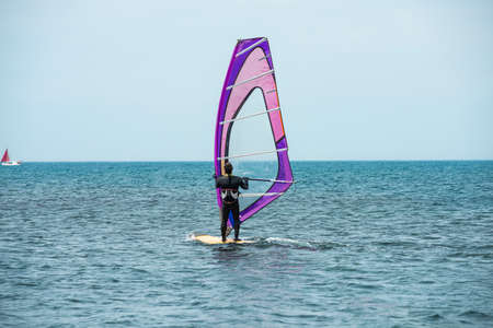 A windsurfer rides on the sea in calm, light wind. The view from the back. Anapa, Russia, Black sea