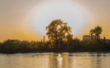 very beautiful and colorful sunrise over the river. The suns rays make their way through the silhouettes of trees