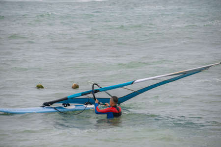 beautiful windsurfer with a board on a tropical beach, makes water start
