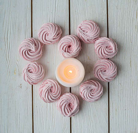 Merengue Marshmallow Zephyr lined in a heart shape with burning candles on a white wooden background. Flat lay. Top view. Pink sweet homemade zephyr or marshmallow. Stock Photo