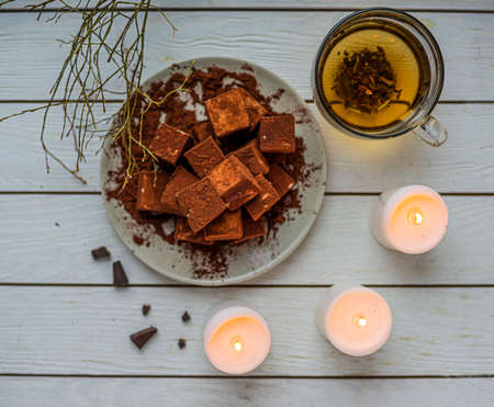 handmade souffle cubes covered with cocoa powder lie on a plate on a light wooden table, hot tea in a glass mug and next to it three white burning candles, pieces of chocolate and a sprig. Top view