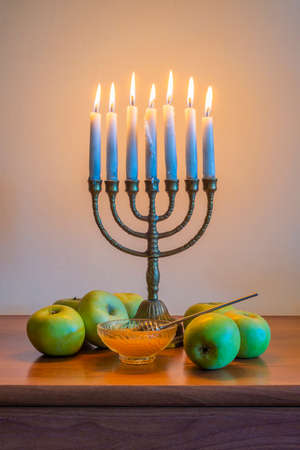 traditional Jewish menorah with burning candles, apples and a glass bowl with honey for the celebration of Hanukkah Stock Photo
