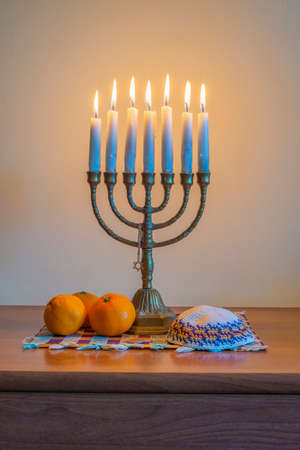traditional Jewish menorah with burning candles, Kippah and a Pile of tangerines on a knitted cloth for the celebration of Hanukkah