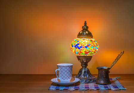 Turkish coffee in cezve, Turk and a traditional old Arabic lamp glows in the dark.