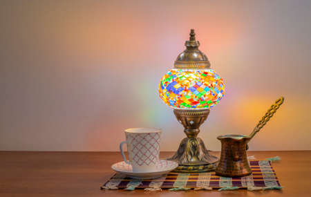 Turkish coffee in cezve, Turk and a traditional old Arabic lamp glows in the dark. Stok Fotoğraf