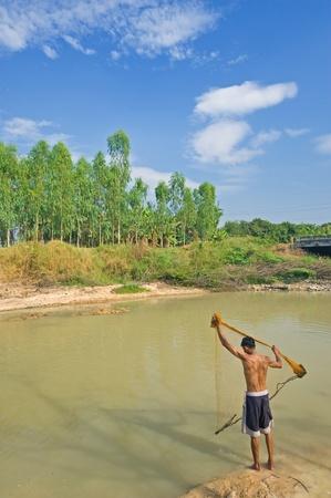 A man throw fishing net in lake