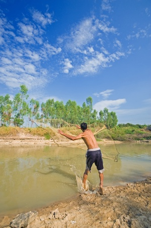 A man throw fishing net in lake  photo